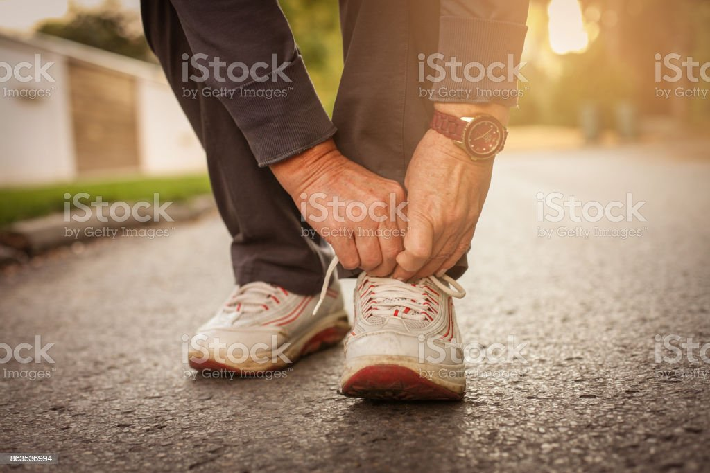 Senior woman hands tying sneakers. Close up. stock photo