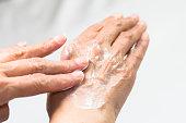 年配の女性の手フレンチ マニキュア ハンド クリーム白い背景の分離を適用します。