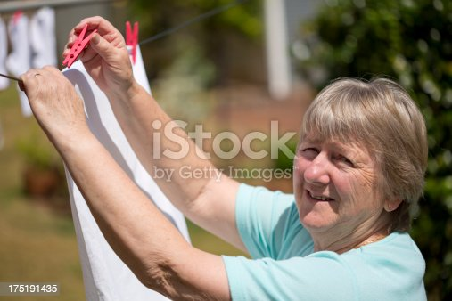 Senior woman hanging clothes on a washing line to dry