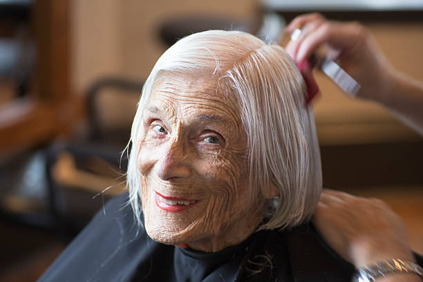 Senior woman happily relaxing at the hairdresser stock photo