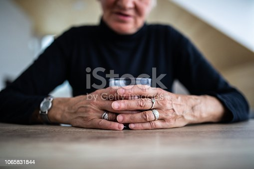 Senior Woman Sitting And Holding Glass Of Refreshing Cold Drink At Home