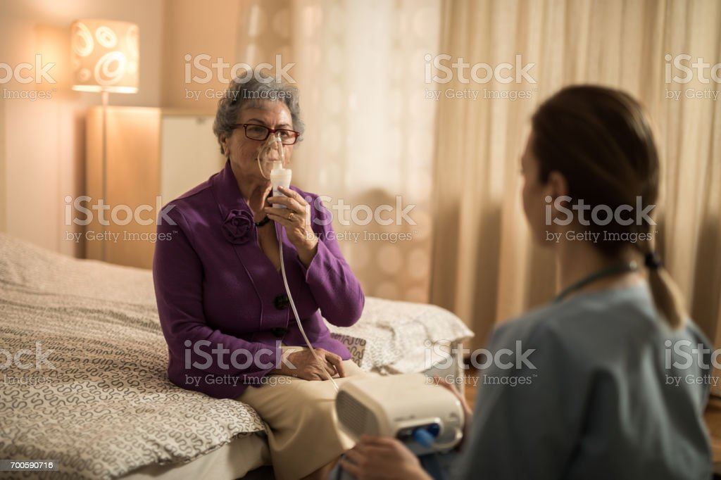 Old woman breathing through oxygen mask while having a visit from a...