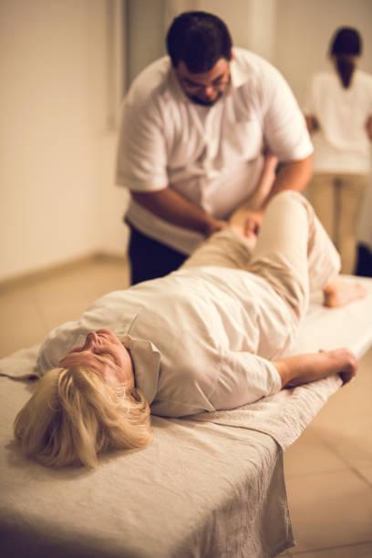 ältere frau, die eine physikalische therapie bei arztpraxis. - chiropraktik wellness stock-fotos und bilder