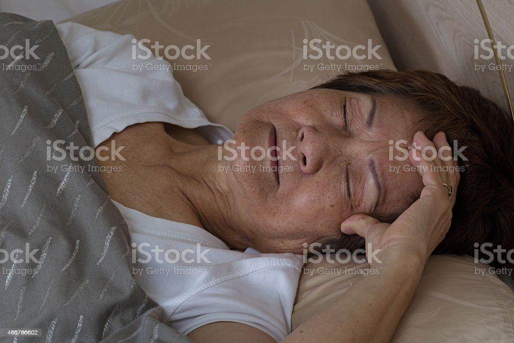 Senior woman having difficulty falling asleep at nighttime stock photo