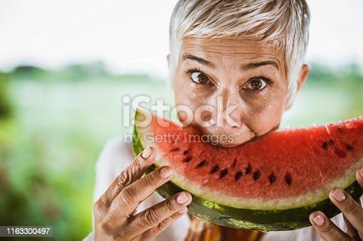 Mature woman biting watermelon and looking at camera.