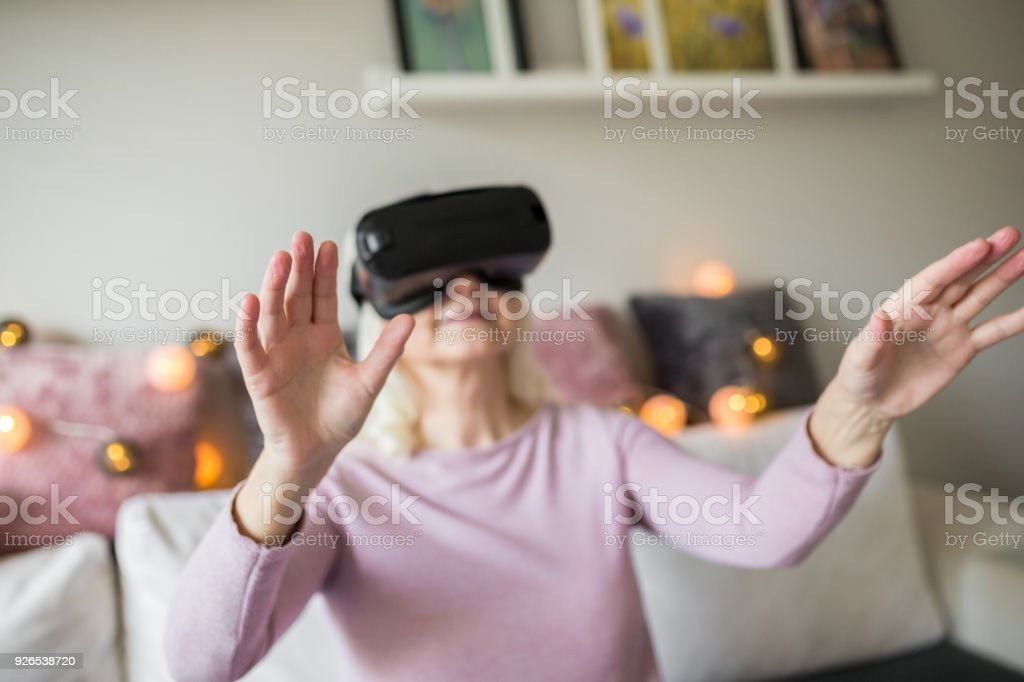 Senior woman having fun with vr headset at home stock photo