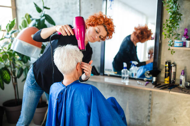 Senior Woman Having Hair Blow Dried by Hairstylist stock photo
