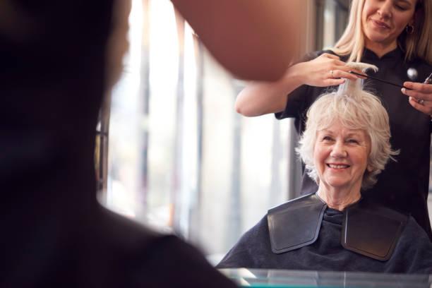 Senior Woman Having Hair Cut By Female Stylist In Hairdressing Salon stock photo