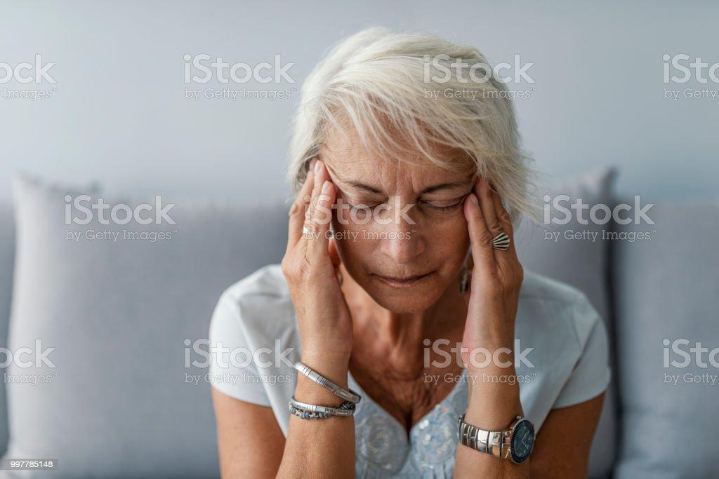 Mujer Senior con dolor de cabeza y tocando sus templos - foto de stock