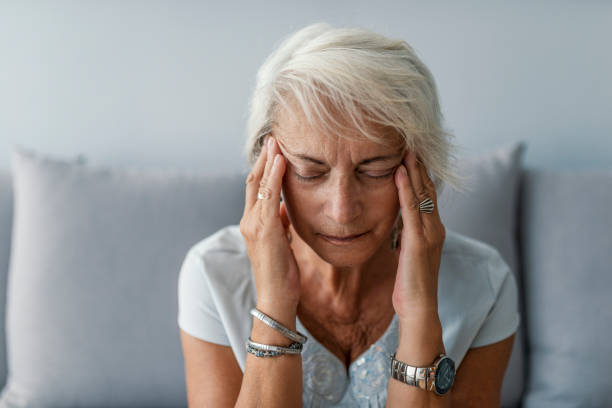Senior woman having headache and touching her temples Senior woman having headache and touching her temples. Mature woman sitting on a white sofa in a home touching her head with her hands while having a headache pain and feeling unwell face down stock pictures, royalty-free photos & images