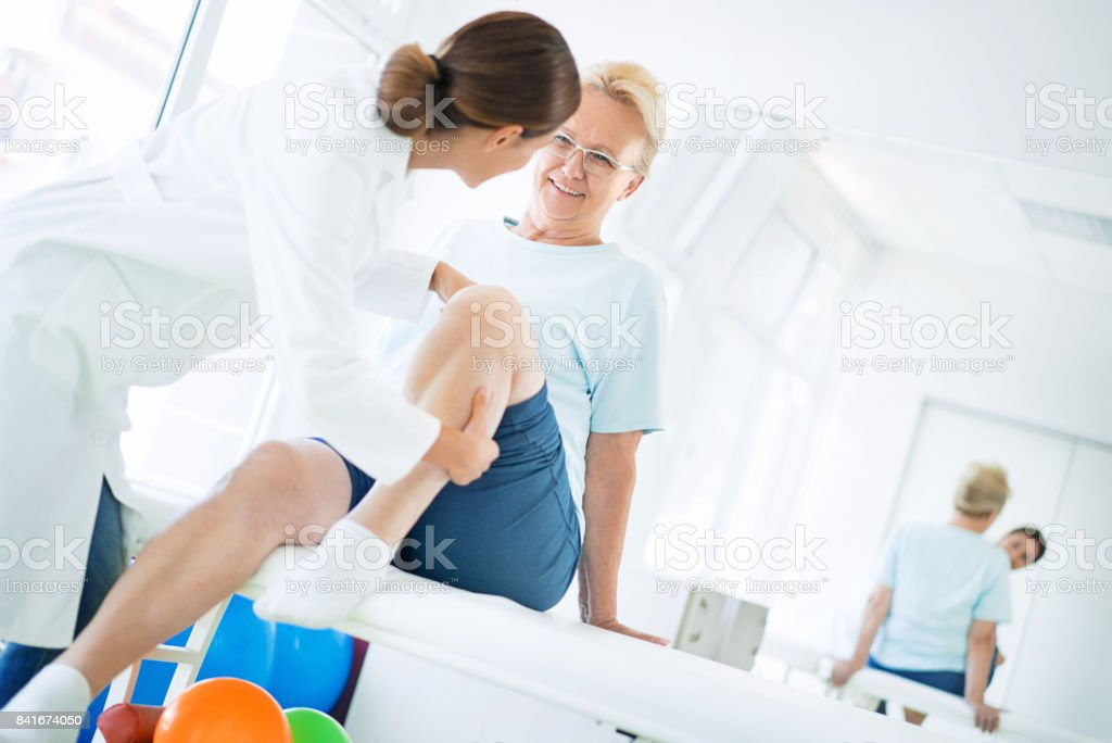 Senior woman having knee examination. stock photo
