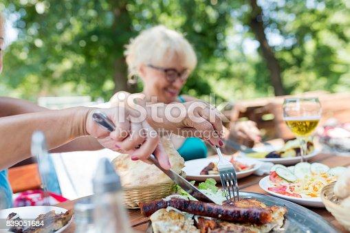istock Senior woman having lunch outdoors 839051684