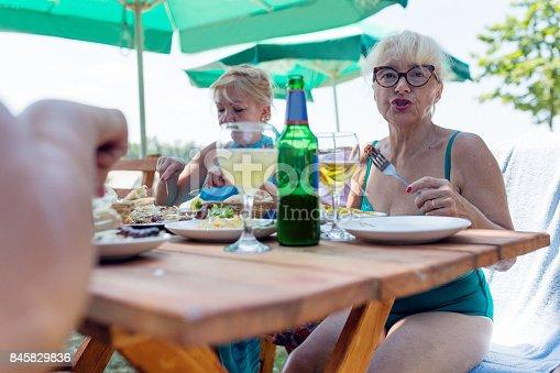 istock Senior woman having lunch outdoors 845829836