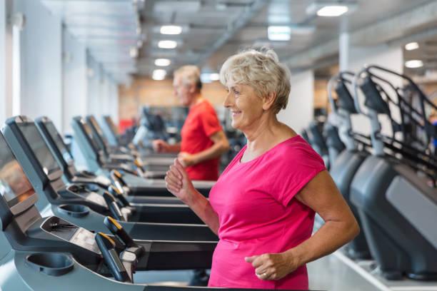 senior woman having rehabilitation at fitness club - runner rehab gym foto e immagini stock