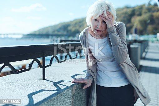 istock Senior woman having vertigo outdoors 936488050