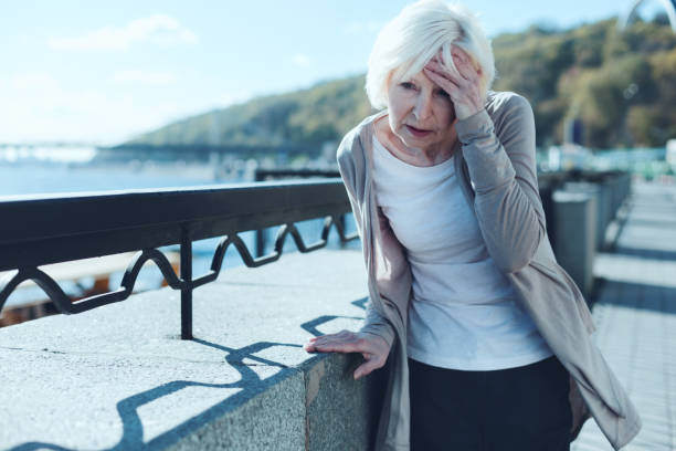 Senior woman having vertigo outdoors stock photo