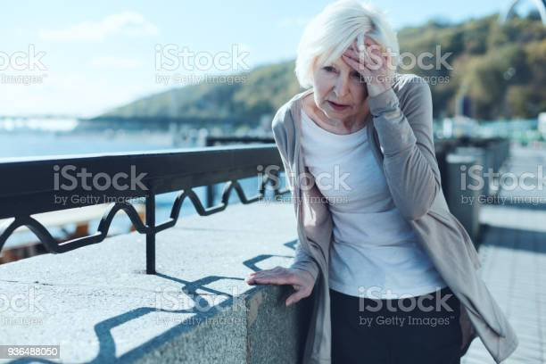 Need to take my pills. Exhausted older lady leaning on a barrier and touching her forehead while suffering from a terrible headache outdoors.