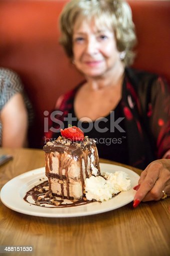 Senior caucasian woman having lunch with friends. She is having a delicious piece of coffee ice cream cake for dessert. There is chocolate sauce on the cake and drizzled on the plate. There is whipped cream on plate and a strawberry on top. Taken with Canon 5D Mark 3. rm