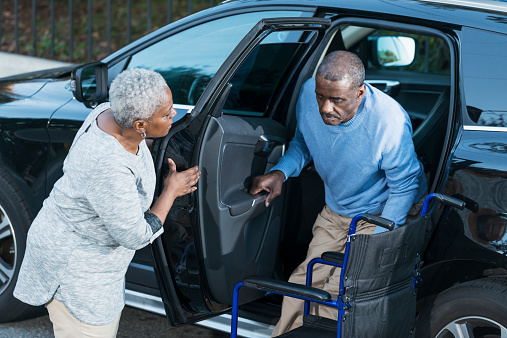 An African American senior woman helping her disabled husband climb out of a car into his wheelchair.