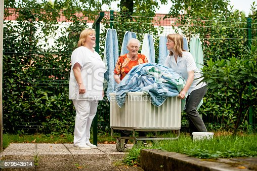 Senior Woman Helping Hanging Laundry On The Washing Line At The Nursing Home, Fresh Air