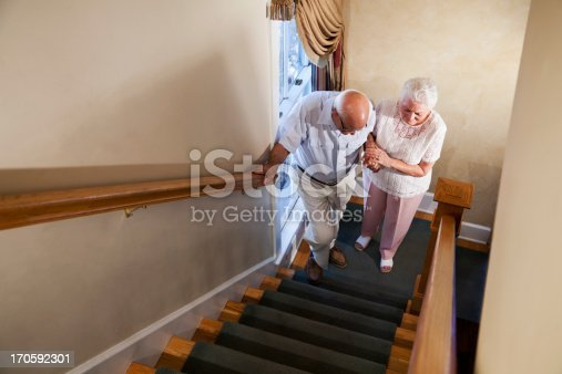 istock Senior woman helping husband climb staircase 170592301