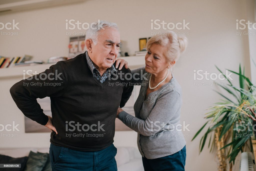 Senior woman helping senior man in a living room who has a back pain stock photo