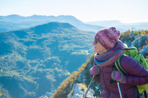 senior woman hiking at autumnal dawn in southern julian alps, europe - all vocabulary foto e immagini stock