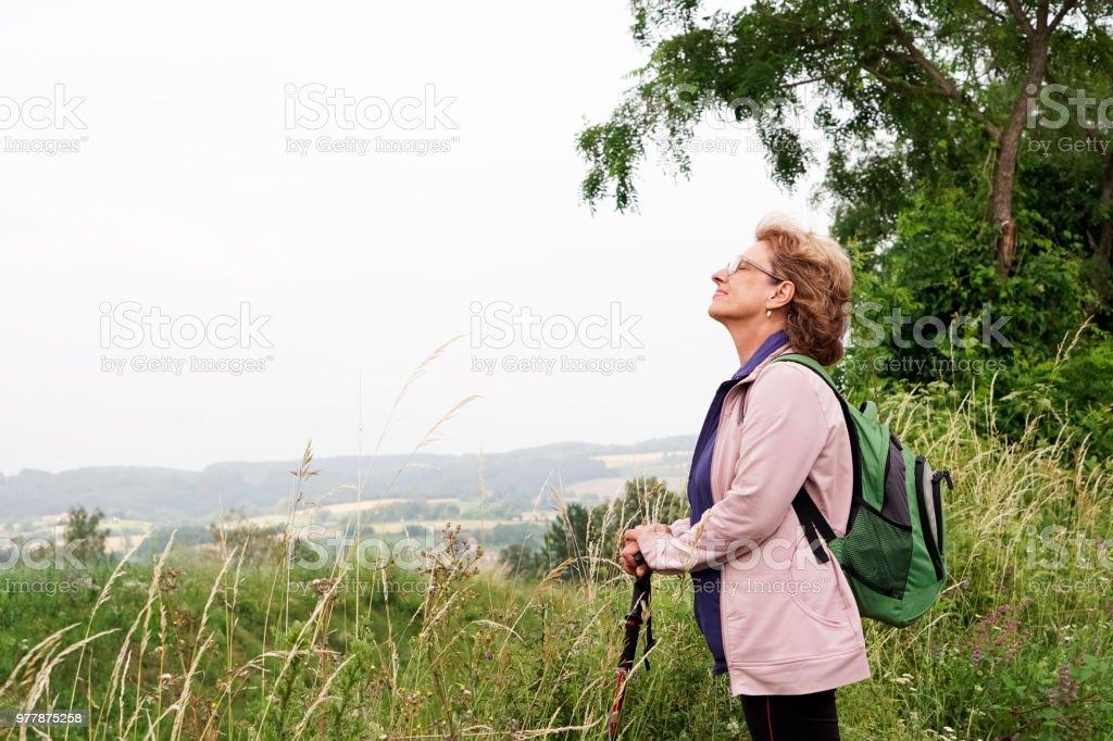 Senior woman hiking on mountain stock photo