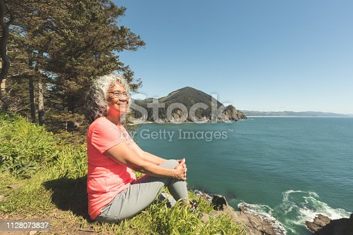 A cute senior woman relaxes on the rocks by a cliff overlooking the ocean. She has been hiking in the forest above the cliffs. A forested mountain range is in the distance and there are rocks jutting out from the ocean below.