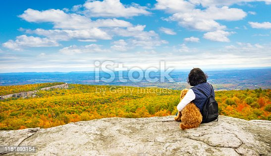 Senior asian woman sitting on the edge of a cliff with her dog and enjoying the fall foliage.