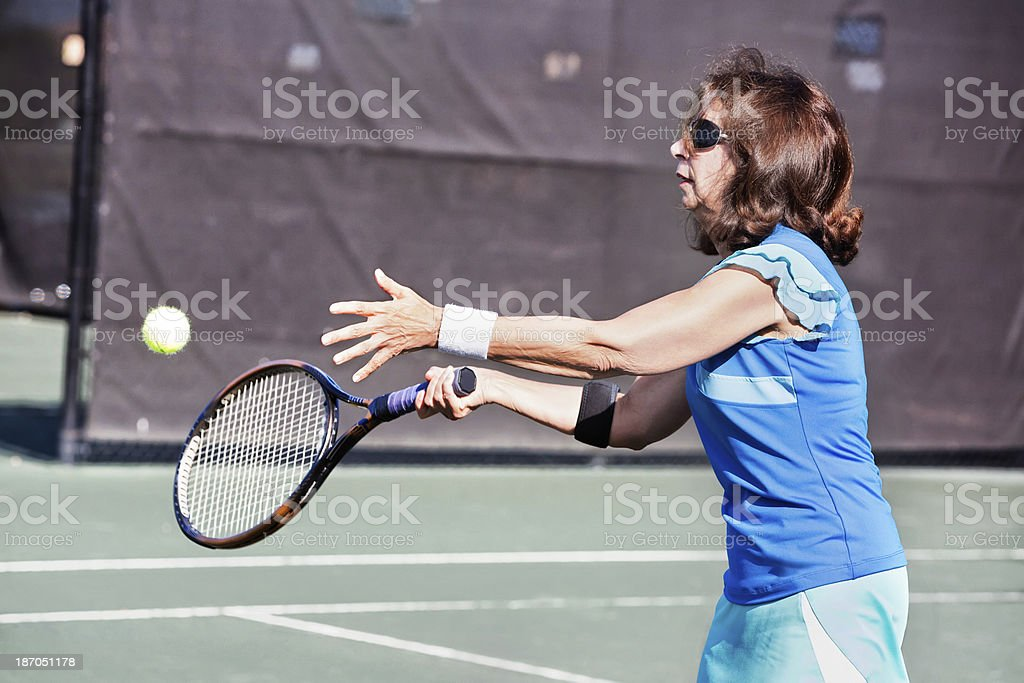 Senior woman hitting a tennis ball royalty-free stock photo