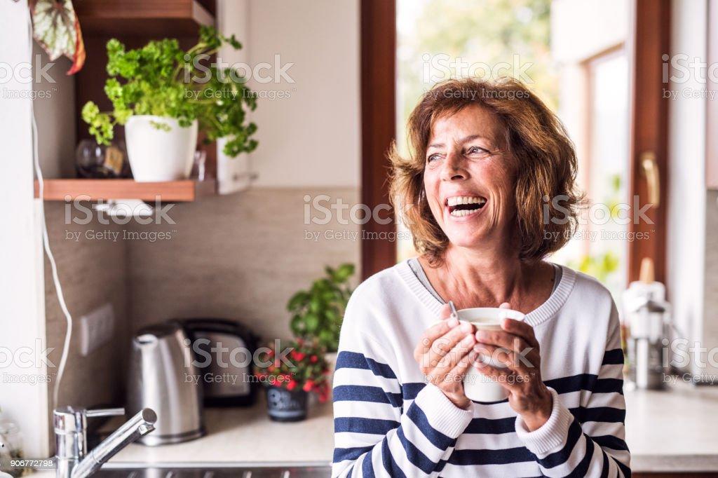 Ältere Frau hält eine Tasse Kaffee in der Küche. – Foto