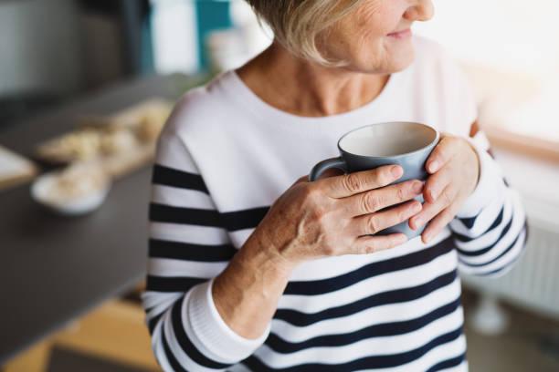 haute femme tenant une tasse de café dans la cuisine. - personne non reconnaissable photos et images de collection