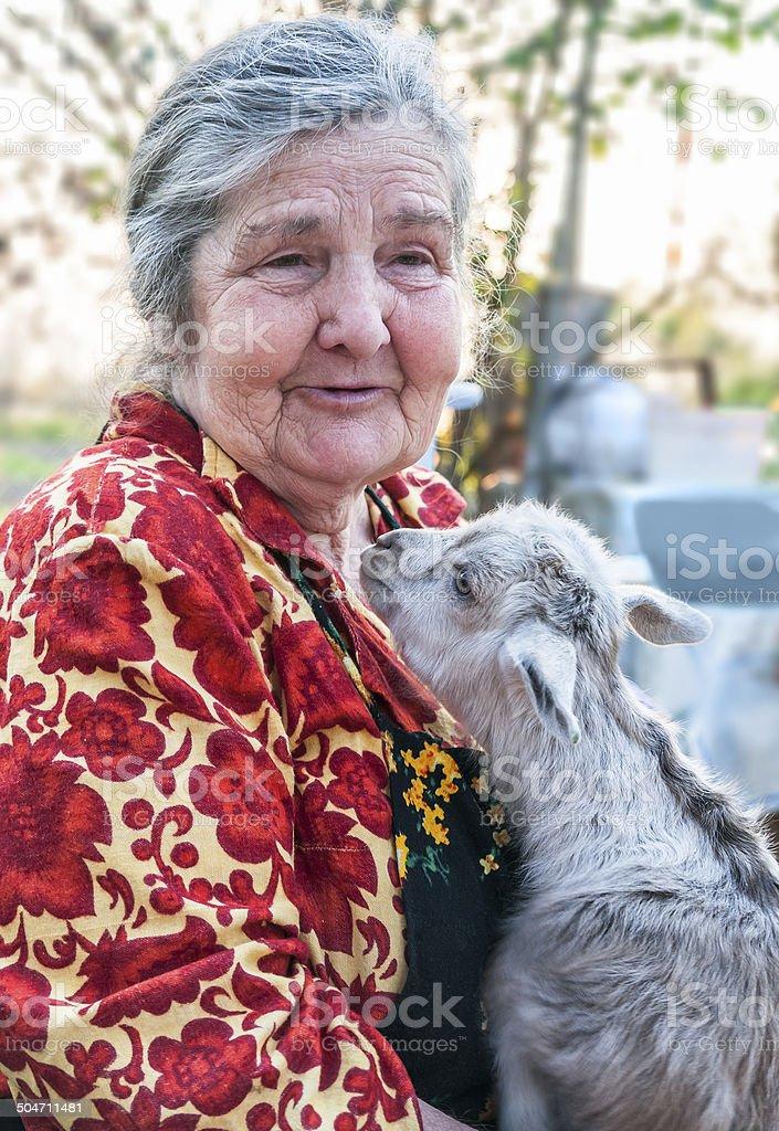 Senior woman holding a goatling stock photo