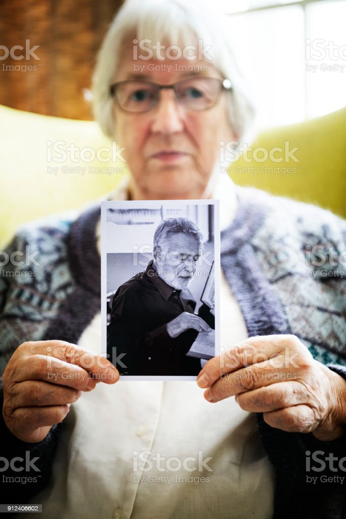 Senior woman holding a photo of a senior man stock photo