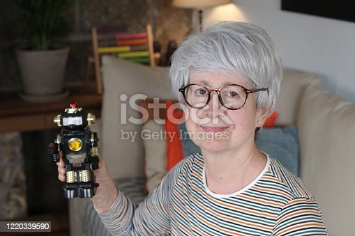 istock Senior woman holding a robot 1220339590