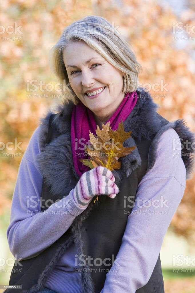 Senior woman holding autumn leaf outdoors royalty-free stock photo