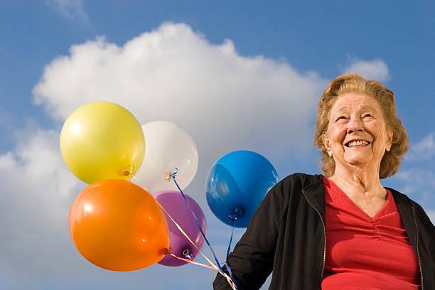 Senior woman holding balloons stock photo