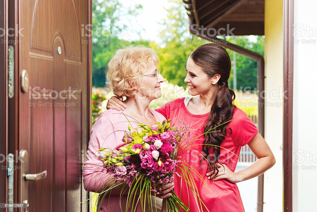 Senior woman holding birthday flowers and hugging to her grandaughter Happy senior woman standing at the entrance house door, holding a birthday bouquet of flowers and hugging to her smiling granddaughter. Outddor shot, vibrant colors. 20-24 Years Stock Photo