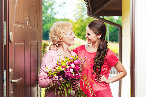 Senior Woman Holding Birthday Flowers And Hugging To Her Grandaughter Stock Photo - Download Image Now