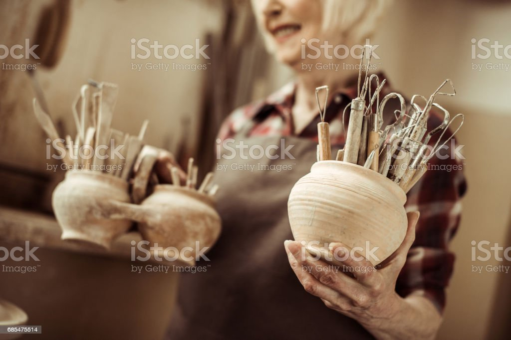 Senior woman holding bowls with pottery tools at at workshop stock photo