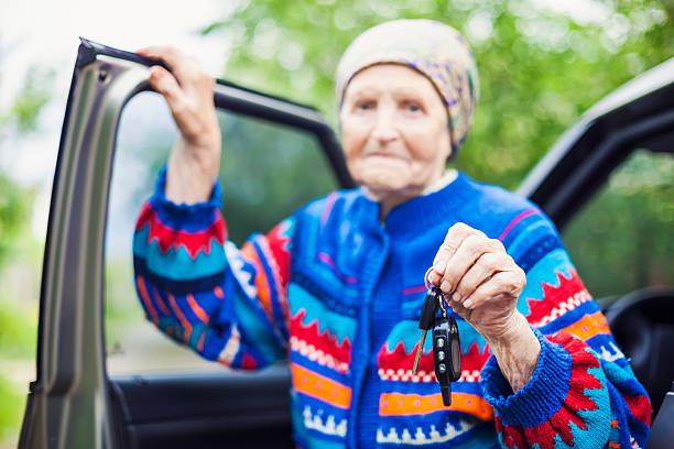 Senior woman holding car key and smiling stock photo