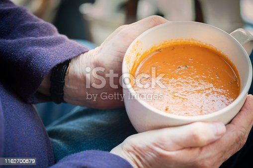 Personal perspective of a woman eating a vegan meal of tomato soup.   Vancouver, British Columbia, Canada.