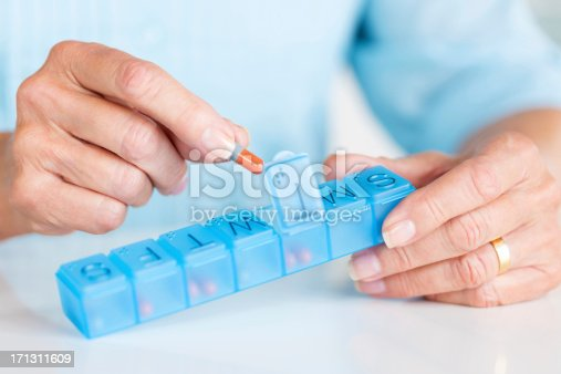 Cropped view of senior woman taking medicine from daily pill container. Horizontal shot.