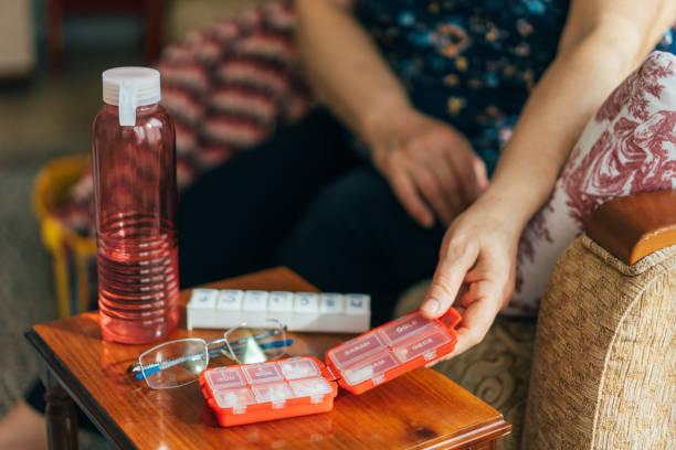senior woman holding daily pill container - доза стоковые фото и изображения