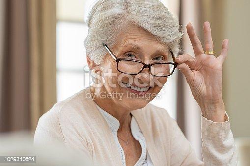 istock Senior woman holding eyeglasses 1029340524