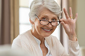 Happy retired senior woman looking at camera while holding eyeglasses. Smiling satisfied woman wearing spectacles at home. Closeup face of old grandmother trying on new eyewear.