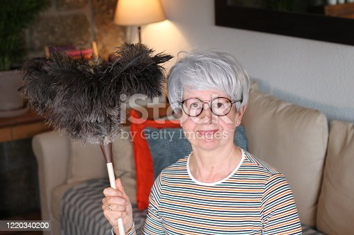 Senior woman holding feather duster.