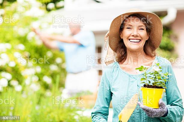 Senior woman holding flower pot and shovel while man gardening picture id506155711?b=1&k=6&m=506155711&s=612x612&h=efdqnx5zma6zm96cimkap mgndfecth3niyu6t7tyjg=