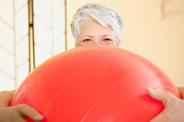 Senior woman holding gymnastic ball close up stock photo